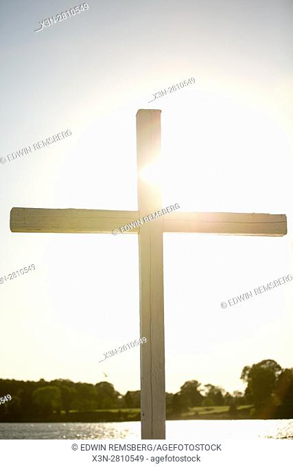 A wooden cross stands with the sunlight behind it