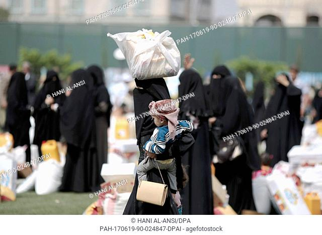 A Yemenite women with a child carries an aid donation by the government of Kuwait in Sanaa, Yemen, 19 June 2017. Unabated conflict and rapidly deteriorating...