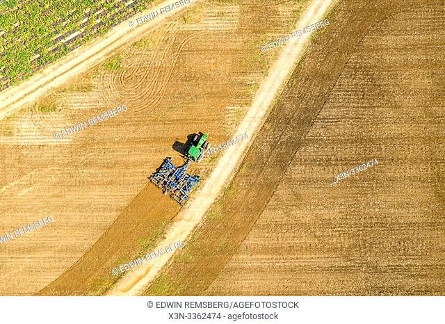 A tractor plows a field in Wyoming, Delaware