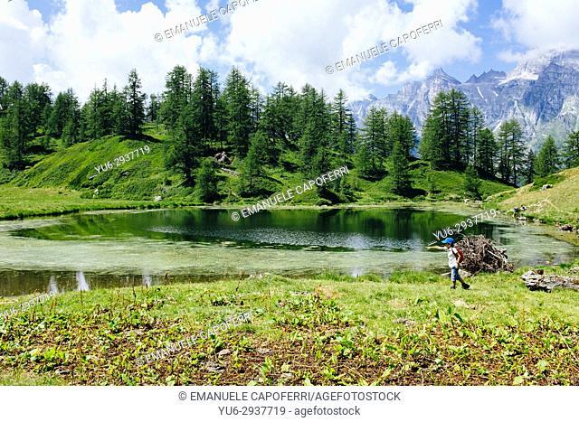 little boys play around a mountain pond. Alpe Devero, Piemonte, Italy