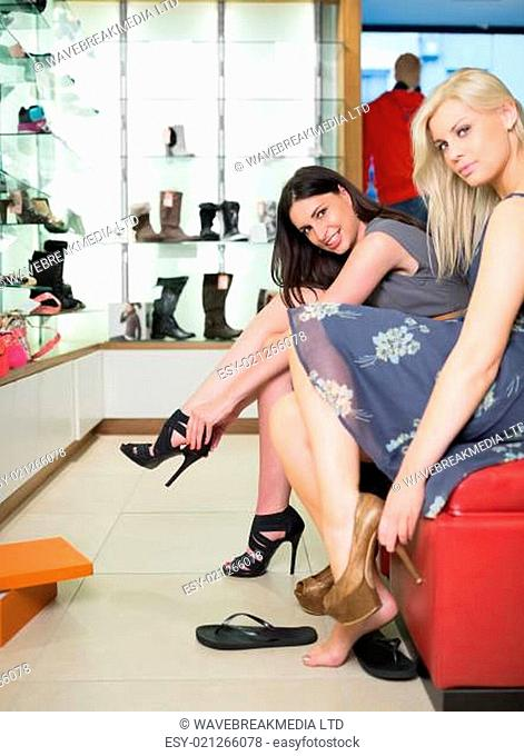 Women smiling and trying on shoes in shoe store