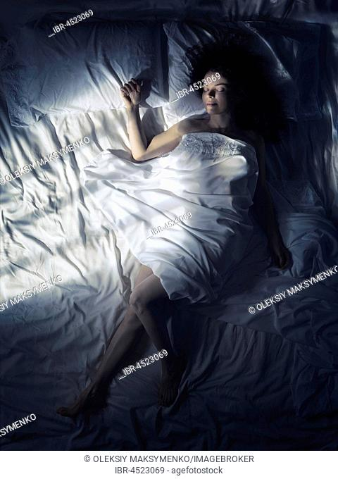 Young woman sleeping alone in bed at night in dark bedroom, lit by moonlight