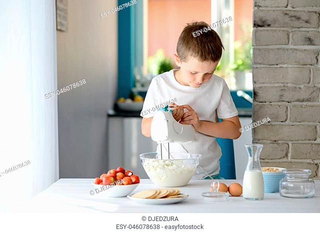 7 year old boy mixing with electric mixer white cottage cheese in a bowl. Prepares mini cheesecakes with strawberries