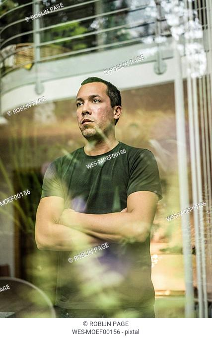 Serious man at home looking out of window