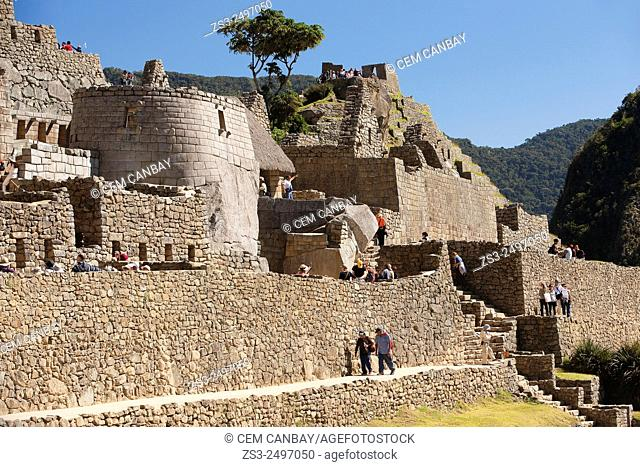 Tourists near the Temple of the Sol at the sacred Inca site of Machu Picchu, Cuzco Region, Peru, South America