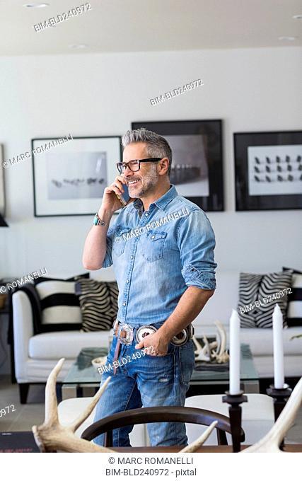 Caucasian man talking on cell phone in livingroom