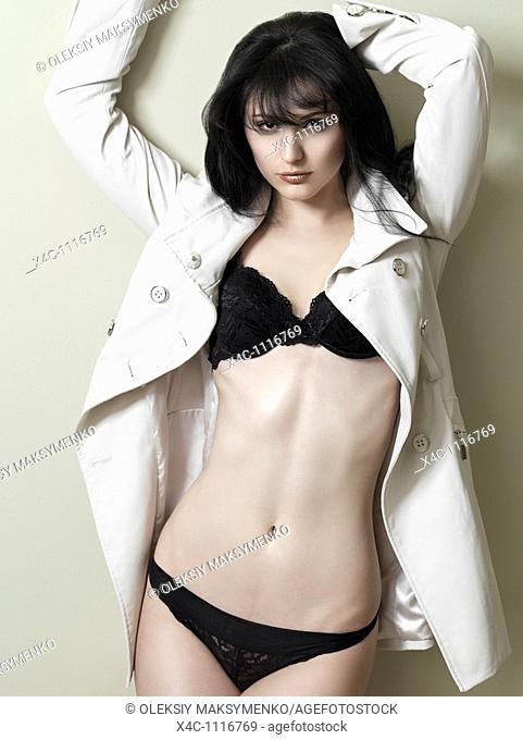 Young beautiful woman in lingerie under a trench
