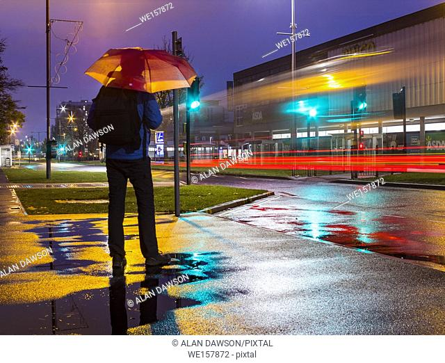 Man with umbrella in early morning rain in Billingham, north east England, United Kingdom