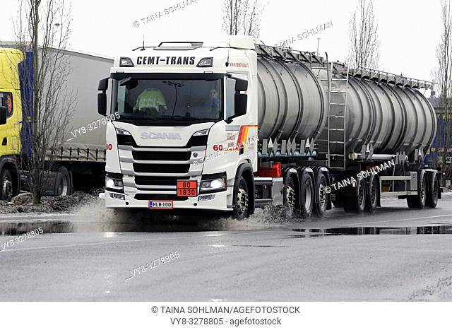 Forssa, Finland - March 16, 2019: Next Generation Scania R500 tank truck for ADR transport drives through small puddle on a rainy day of early spring