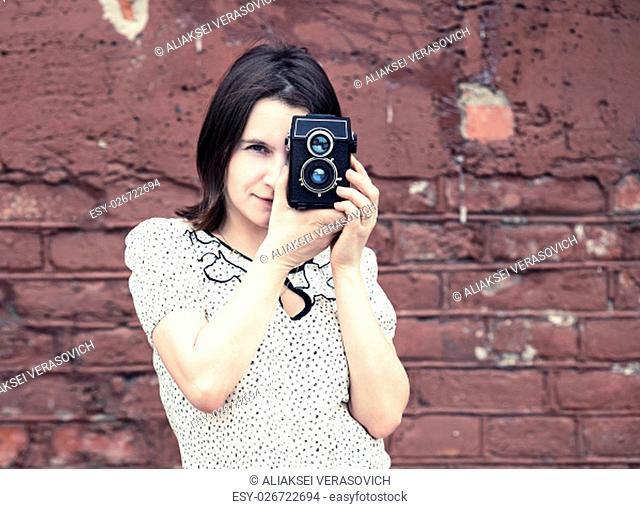 Pretty young woman with vintage camera against brick wall background. Girl taking photo outdoor. Selective focus on model. Retro style photo
