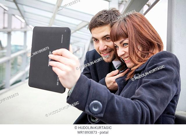 Young couple in airport building taking a self portrait