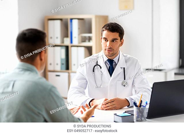 doctor with laptop and male patient at hospital