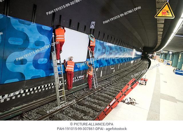 """15 October 2019, Hamburg: Workers assemble a video wall at the S-Bahn station """"""""Landungsbrücken"""""""". S-Bahn passengers only need a few days of patience before the..."""
