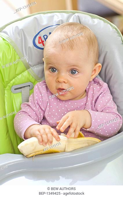 Baby girl eating in a high chair