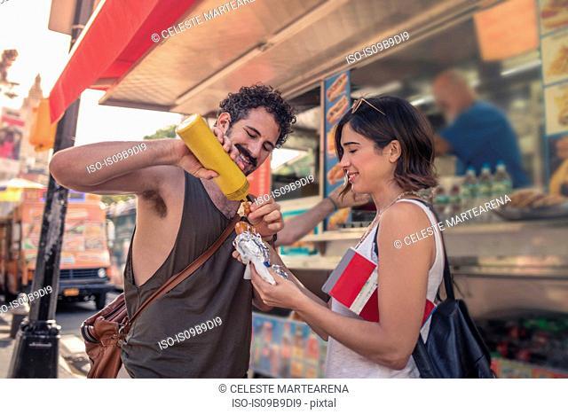 Happy tourist couple putting mustard on take away pretzel on street, Manhattan, New York, USA