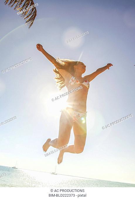 Caucasian woman in bikini jumping for joy