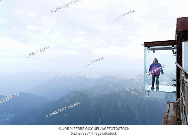 Woman in a crystal box on the void, Pas dans le Vide - step into the void - at 3842 m, Aiguille du Midi, Chamonix-Mont-Blanc, Haute-Savoie, France, Europe