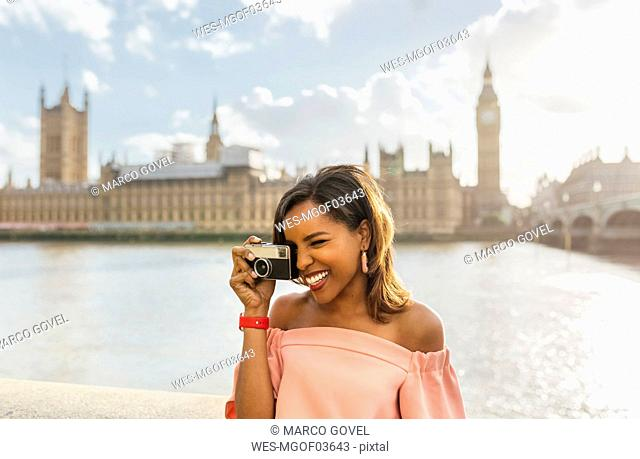 UK, London, beautiful woman taking a picture near Westminster Bridge