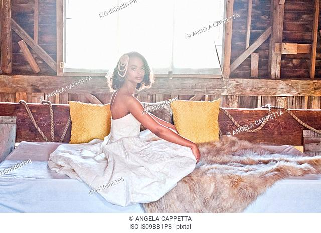 Portrait of bride wearing wedding dress, sitting in barn