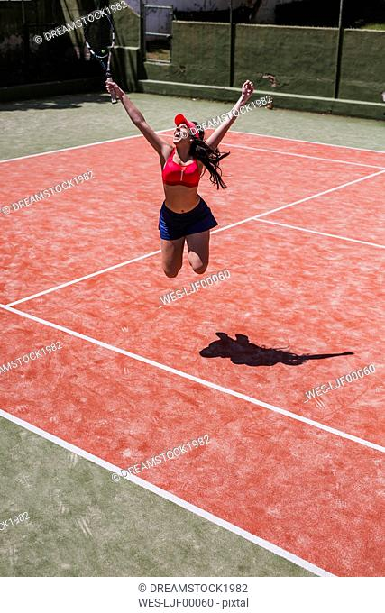 Excited female tennis player cheering on court