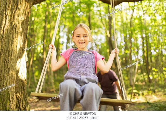 Portrait smiling girl swinging on rope swing in forest