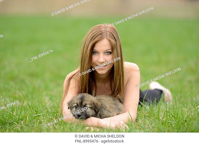 Young woman with a mixed breed dog puppy in garden