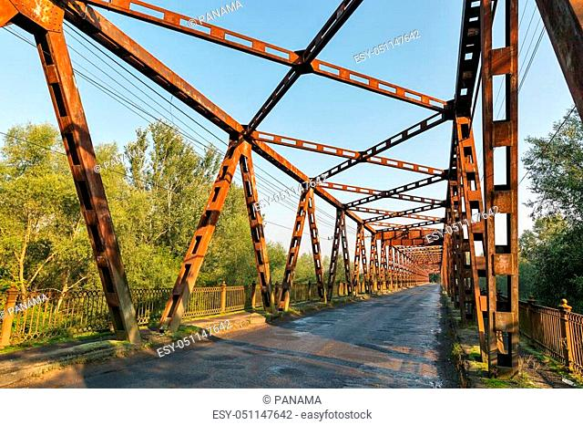 Old rusty empty bridge over Tisa river in Vylok, close to border with Hungary. It is a village in western Ukraine, Zakarpattia region