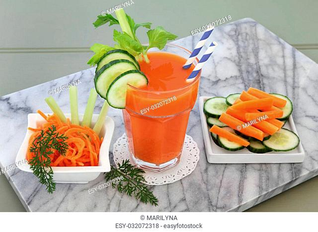 Carrot, celery and cucumber health drink with sliced vegetables on a marble slab over wooden green background