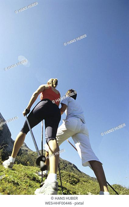 Couple practising nordic walking in mountains, rear view