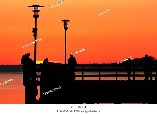 silhouettes of people standing on the dock early in the morning and waiting for sunrise