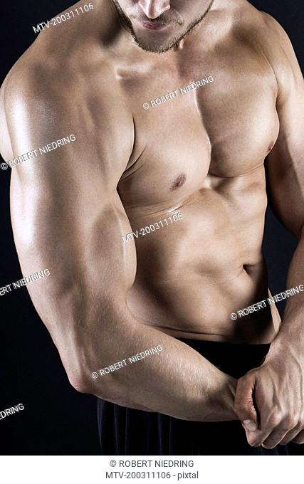 Close-up of shirtless body builder flexing muscles