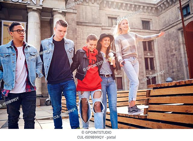 Five young adult friends walking together in city