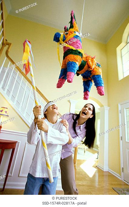 Girl wearing a blindfold hitting a pinata with a stick