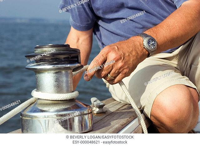 Man tying a line on a winch on a sailboat