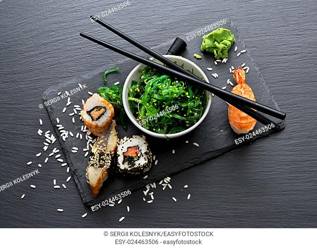 Sushi and seaweed salad on slate table