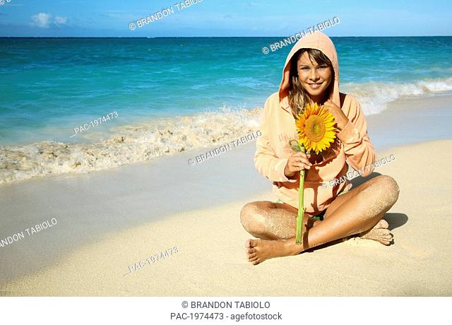 Hawaii, Oahu, Lanikai, Attractive Young Woman On The Beach With Sunflower