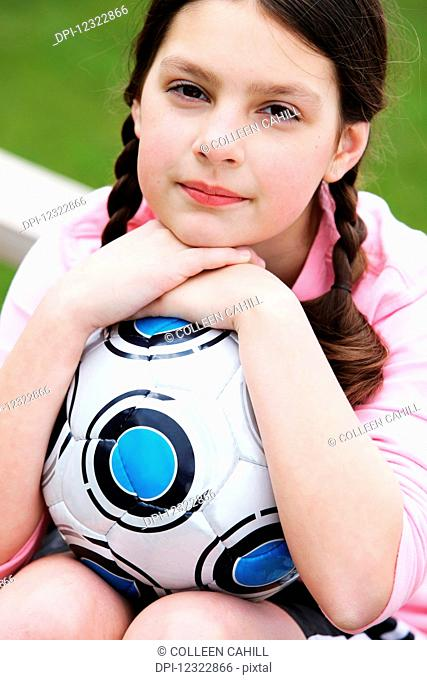 Portrait of a young girl with her soccer ball; Oregon, United States of America