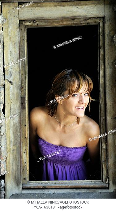 Portrait of a smiling young woman standing in window frame