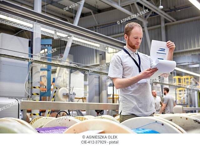 Male supervisor with clipboard checking inventory in fiber optics factory