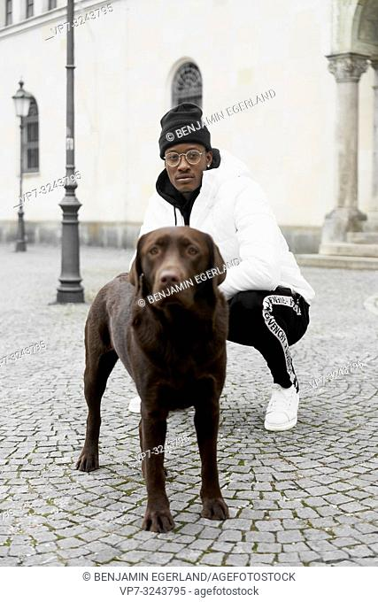 stylish man with dog, in city Munich, Germany