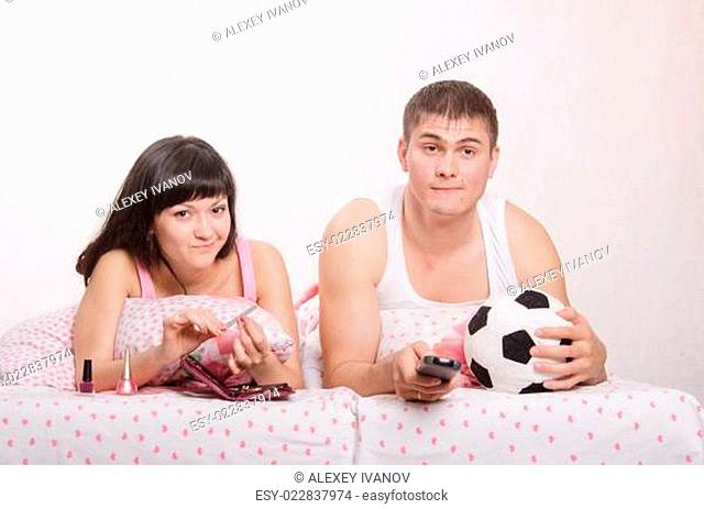 Man watching soccer on TV, manicure girl engaged in bed
