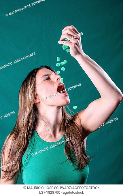 Young woman in green dropping green candy pieces in her mouth