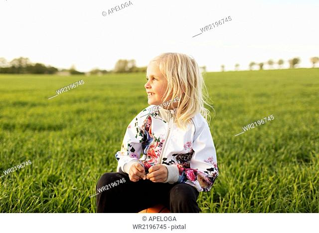 Thoughtful girl looking away while sitting on basketball at grassy field