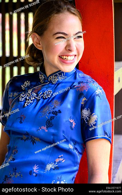 A laughing 14 year old brunette girl in an asian style dress
