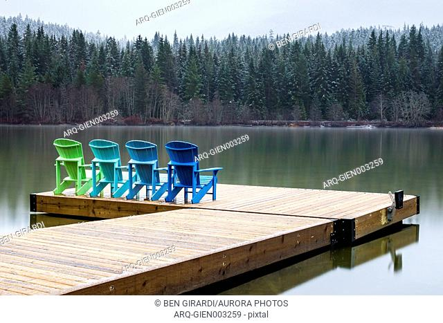 Four Adirondack Chairs Sit On A Dock On Green Lake In Whistler, British Columbia