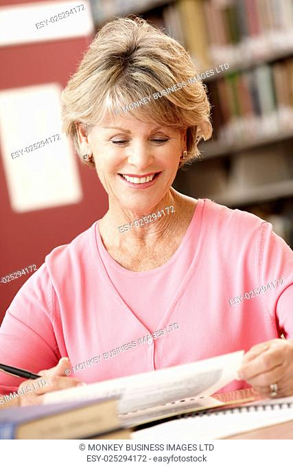 Mature student working in library