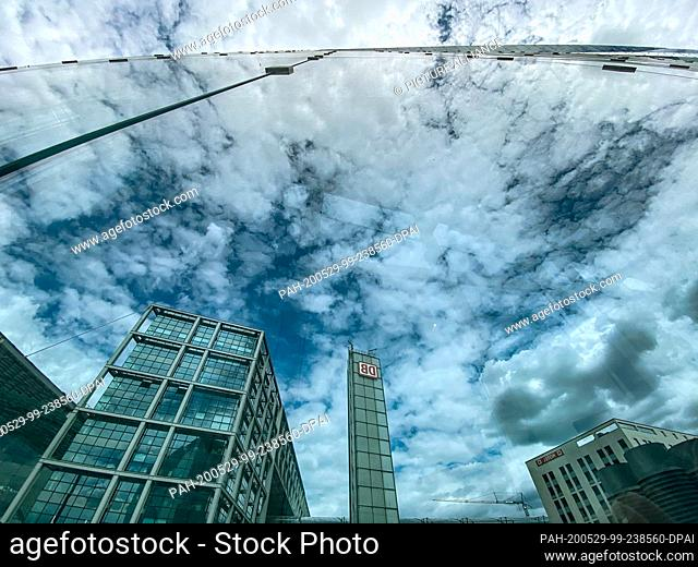 29 May 2020, Berlin: Clouds and the main station are reflected in the glass facade of the Cube Berlin high-rise building at the main station
