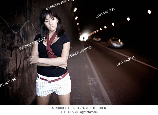 Latin woman in shorts standing in a tunnel