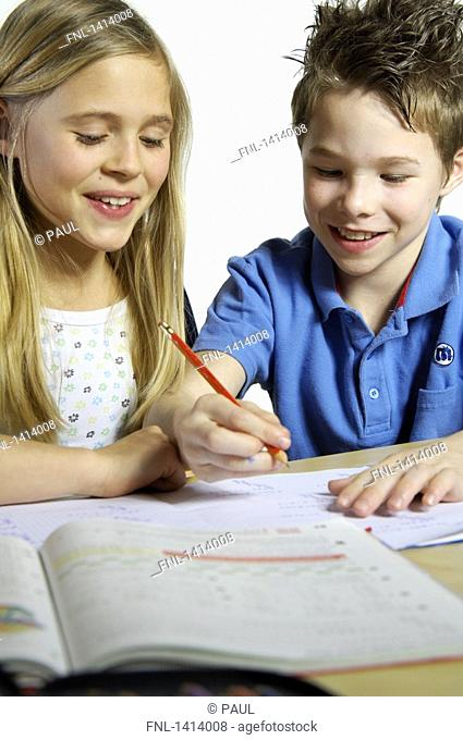 Close-up of brother and sister studying and smiling