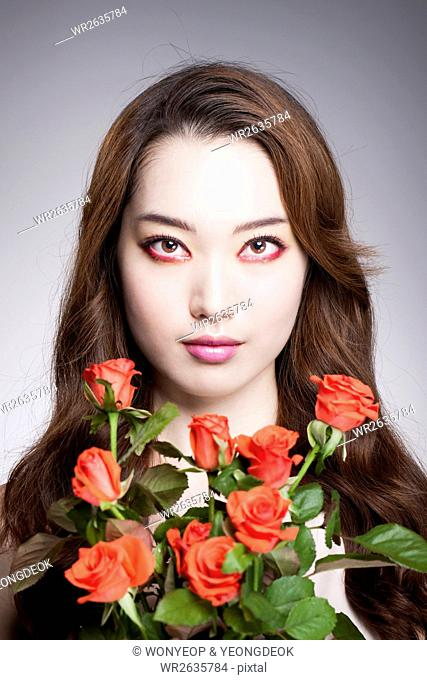Portrait of young Korean woman in rwd eye liner with red roses